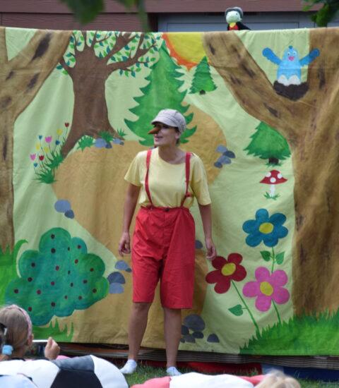 aktorka w przebraniu Pinokio stoi na tle teatralnej ścianki, na której siedzi zielony robaczek