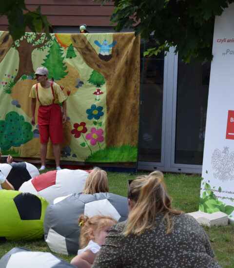 aktorka w przebraniu Pinokio stoi na tle teatralnej ścianki, na której siedzi zielony robaczek, z boku ustawiony kolorowy rollup