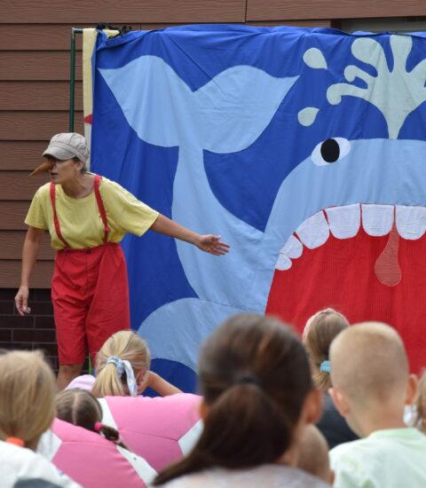 aktorka w przebraniu Pinokio stoi na tle teatralnej ścianki, na której widoczny jest niebieski wieloryb