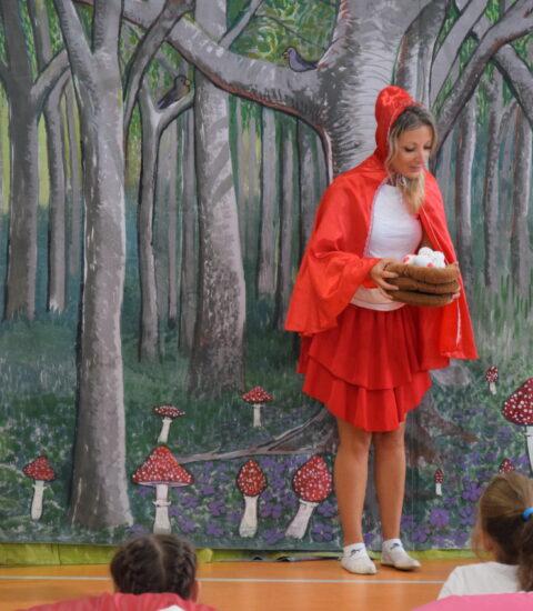 kobieta w przebraniu Czerwonego Kapturka w rękach trzyma gniazdo z jajkami stoi pomiędzy chłopcem i dziewczynki