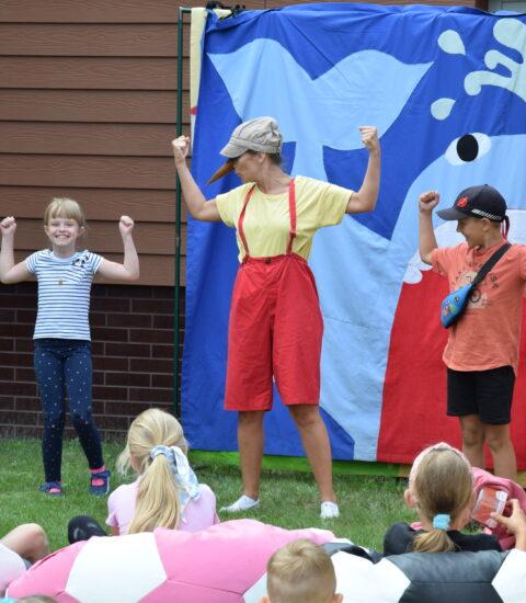 aktorka w przebraniu Pinokio stoi na tle teatralnej ścianki, na której widoczny jest niebieski wieloryb, obok stoi chłopiec i dziewczynka z uniesionymi rękoma