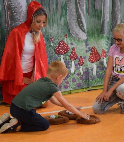 kobieta w przebraniu Czerwonego Kapturka klęczy pomiędzy chłopcem i dziewczyną