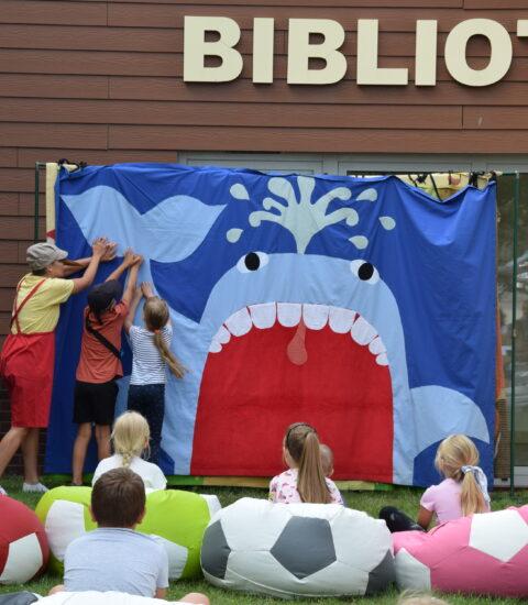 aktorka w przebraniu Pinokio, chłopiec i dziewczynka stoją odwróceni w stronę teatralnej ścianki, na której widoczny jest niebieski wieloryb