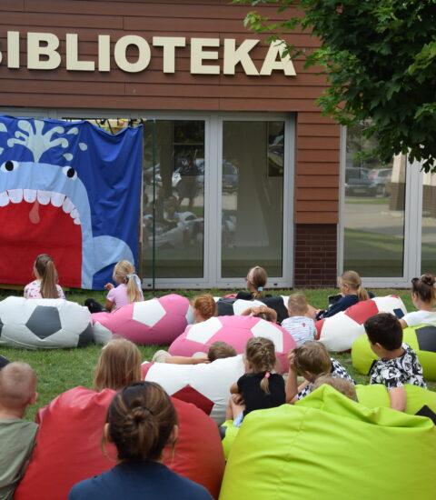aktorka w przebraniu Pinokio, chłopiec i dziewczynka stoją odwróceni w stronę teatralnej ścianki, na której widoczny jest niebieski wieloryb, na trawie siedzą dzieci na kolorowych pufach