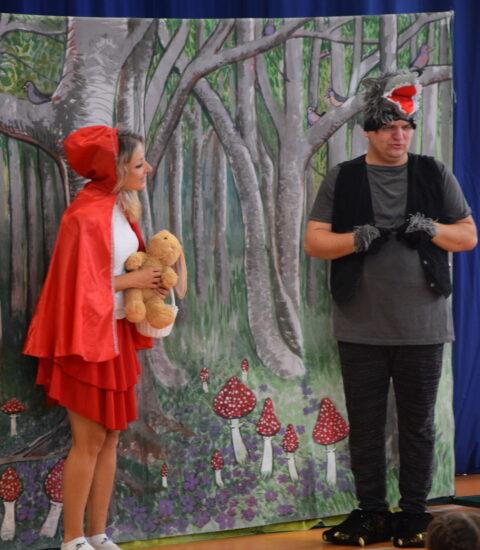 kobieta w przebraniu Czerwonego Kapturka stoi na tle imitacji lasu, obok mężczyzna przebrany za wilka