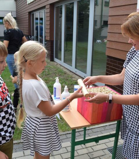 kobieta w sukience w kratkę podaje dziewczynce tekturową tubę, w tle budynek biblioteki
