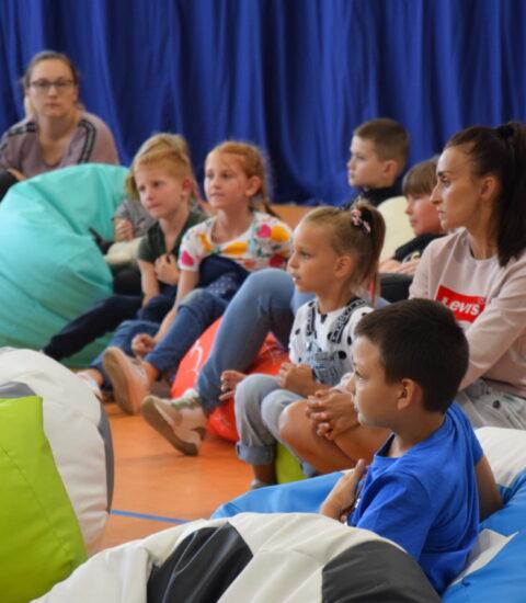 publiczność siedząca na kolorowych pufach
