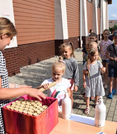 kobieta w sukience w kratkę podaje dziewczynce tekturową tubę, w tle budynek biblioteki, dalej dzieci czekające w kolejce