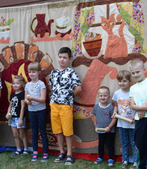 grupa dzieci stojąca na tle ścianki teatralnej