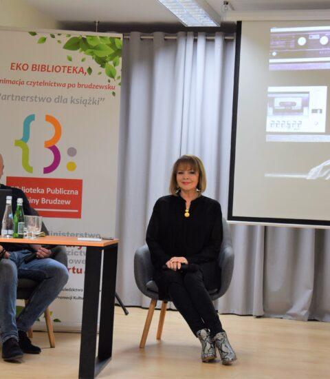 kobieta ubrana na czarno i mężczyzna siedzą na fotelach przy stoliku, na którym leży laptop i stoją butelki z wodą, za nimi kolorowy rollup, po prawej stronie ekran, na którym wyświetlane jest zdjęcie
