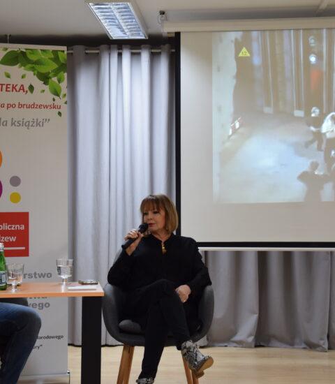 kobieta ubrana na czarno, siedzi w fotelu, w prawej ręce trzyma mikrofon, w tle ekran, na którym wyświetlane jest zdjęcie, z lewej strony stoi kolorowy rollup
