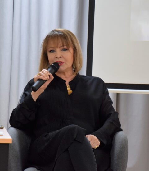 kobieta ubrana na czarno, siedzi w fotelu, w prawej ręce trzyma mikrofon, w tle ekran, na którym wyświetlane jest zdjęcie