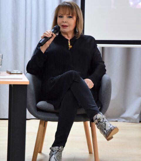 kobieta ubrana na czarno siedzi na fotelu przy stoliku, w ręku trzyma mikrofon
