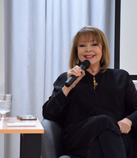 kobieta siedząca przy stoliku, w ręku trzymają mikrofon