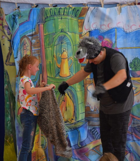 mężczyzna w przebraniu wilka, obok dziewczynka w rękach trzyma sweter