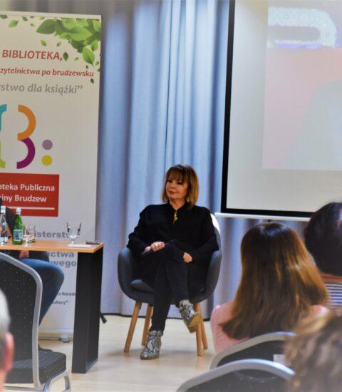 kobieta ubrana na czarno i mężczyzna siedzą na fotelach przy stoliku, na którym leży laptop i stoją butelki z wodą, za nimi kolorowy rollup, po prawej stronie ekran, na którym widać zdjęcie mężczyzny
