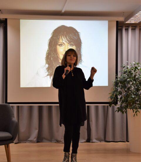 kobieta ubrana na czarno stoi, w ręku trzyma mikrofon, ma uniesioną lewą rękę, za nią ekran, na którym wyświetlane jest zdjęcie kobiety, w tle szara zasłona