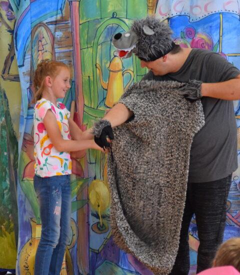 mężczyzna w przebraniu wilka, obok dziewczynka zakłada wilkowi ubranie