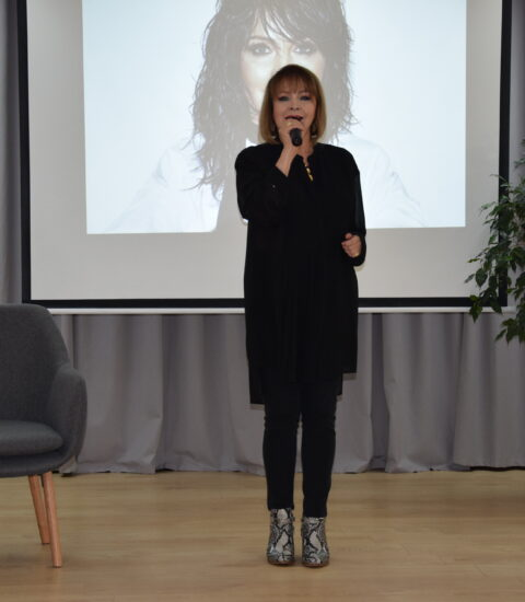 kobieta ubrana na czarno stoi, w ręku trzyma mikrofon, za nią ekran, na którym wyświetlane jest zdjęcie kobiety, w tle szara zasłona