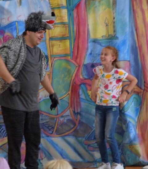 mężczyzna w przebraniu wilka, obok śmiejąca się dziewczynka