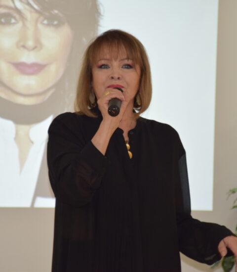 kobieta ubrana na czarno, stoi, w prawej ręce trzyma mikrofon, w tle ekran, na którym wyświetlane jest zdjęcie kobiety