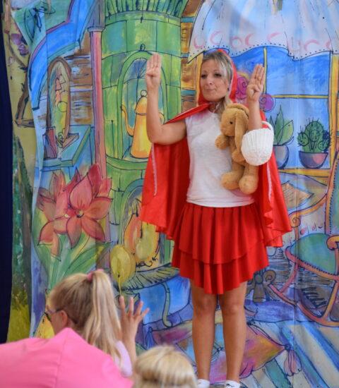kobieta w przebraniu Czerwonego Kapturka zaciska kciuki