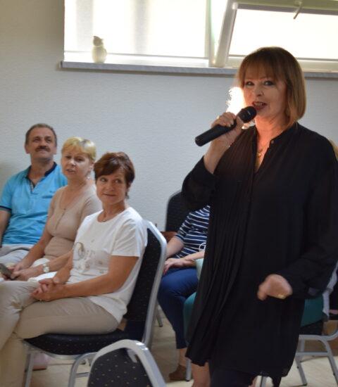 kobieta ubrana na czarno trzyma mikrofon w prawej , stoi pomiędzy publicznością siedzącą na krzesłach
