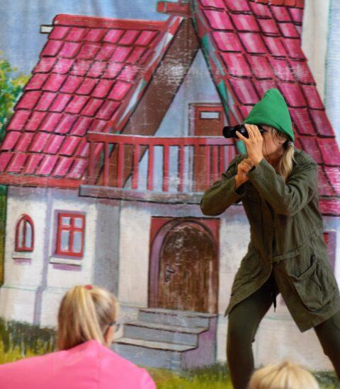 aktorka w przebraniu leśniczego patrzy przez lornetkę