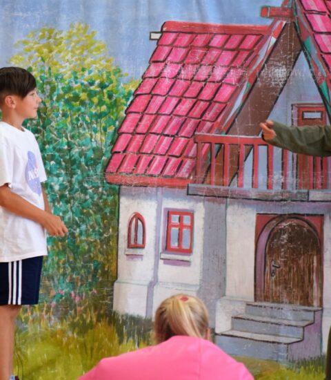 aktorka w przebraniu leśniczego zwrócona w stronę stojącego obok chłopcaaktorka w przebraniu leśniczego zwrócona w stronę stojącego obok chłopca