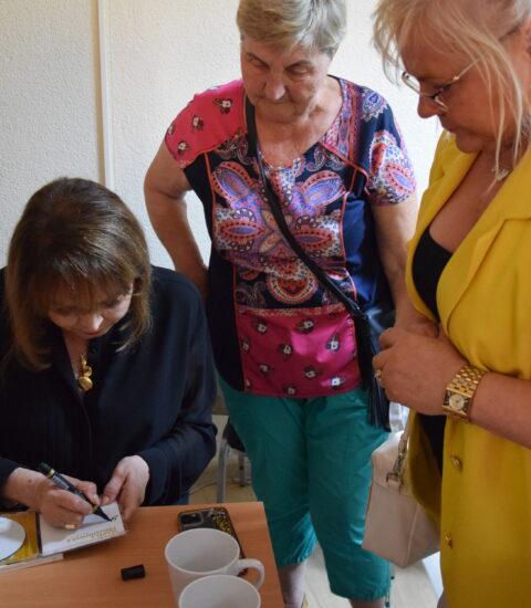 kobieta siedząca przy stoliku podpisuje płytę, dwie kobiety stojące obok niej