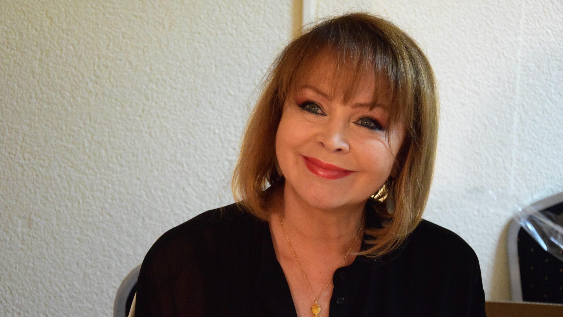 uśmiechnięta kobieta we włosach do ramion, ubrana w czarną bluzkę