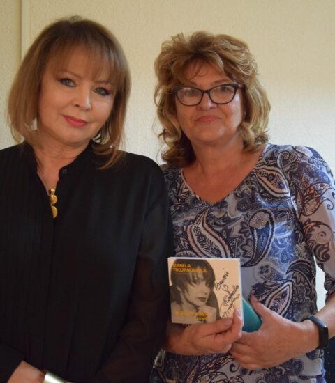 dwie kobiety stojące obok siebie, jedna z nich w rękach trzyma płytę