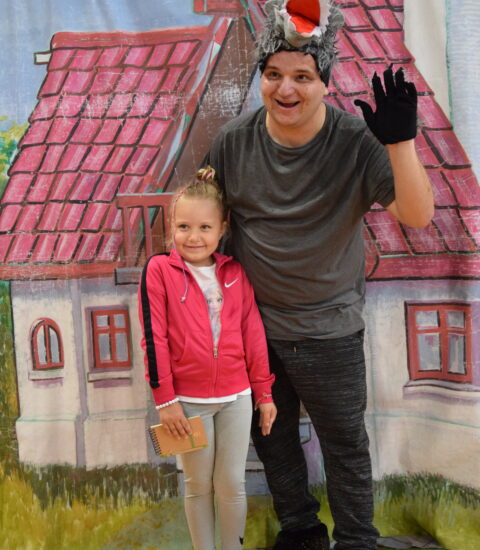 mężczyzna w przebraniu wilka stoi na tle imitacji domu, obok dziewczynka