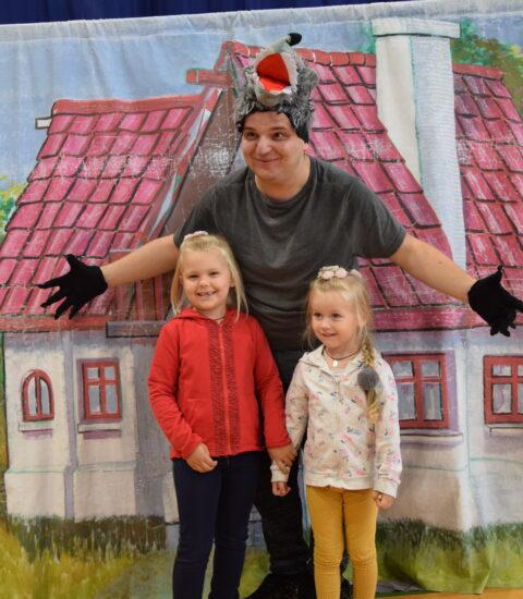 mężczyzna w przebraniu wilka stoi na tle imitacji domu, obok dwie dziewczynki