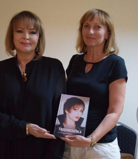 dwie kobiety stojące obok siebie, w rękach trzymają książkę