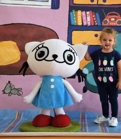 dziewczynka stoi obok dużej maskotki na tle ścianki imitującej pokój