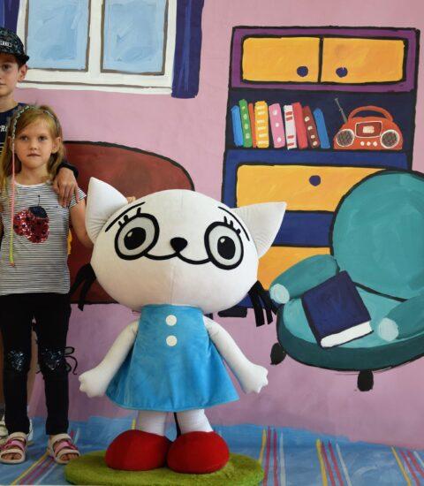 chłopiec i dziewczynka stoją obok dużej maskotki na tle ścianki imitującej pokój