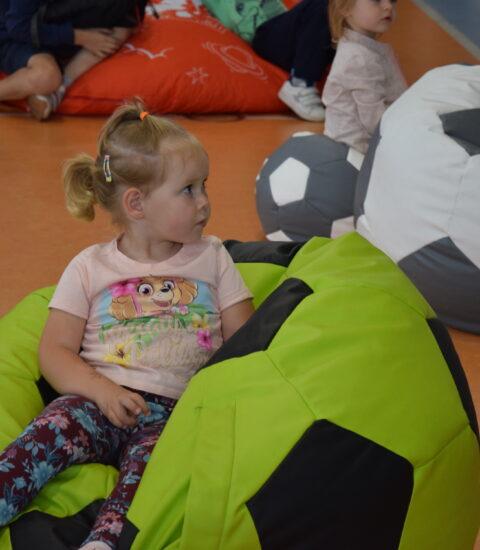 mała dziewczynka siedzi na kolorowej pufie