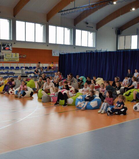 publiczność na sali, dzieci siedzą na kolorowych pufach