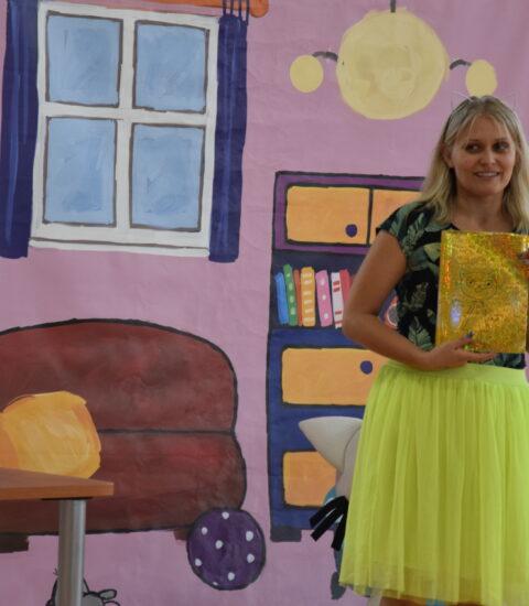 kobieta w żółtej spódnicy stoi, a rękach trzyma książkę z żółtą okładką, za nią ściana imitująca pokój
