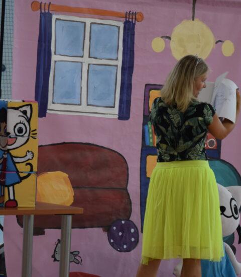 kobieta w żółtej spódnicy stoi tyłem w rękach trzyma otwartą książkę, za nią ściana imitująca pokój