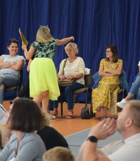 kobieta w żółtej spódnicy na tle publiczności trzyma prawą rękę nad głową siedzącej kobiety