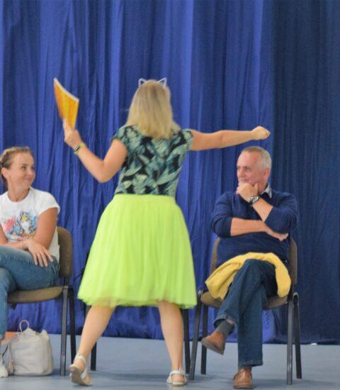 kobieta w żółtej spódnicy na tle publiczności trzyma prawą rękę nad głową siedzącego mężczyzny