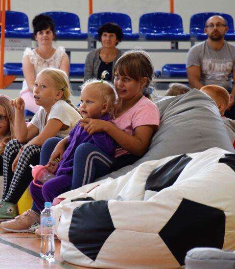 dzieci siedzące na kolorowych pufach, w tle dwie kobiety i mężczyzna siedzący na trybunach