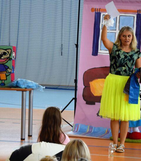kobieta w żółtej spódnicy w prawej ręce uniesionej do góry trzyma kartę papieru, w lewej worki na śmieci
