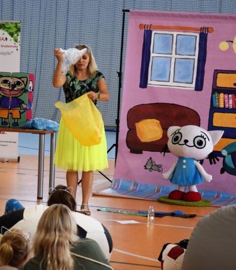 kobieta w żółtej spódnicy w prawej ręce uniesionej do góry trzyma torbę foliową, w lewej worek na śmieci