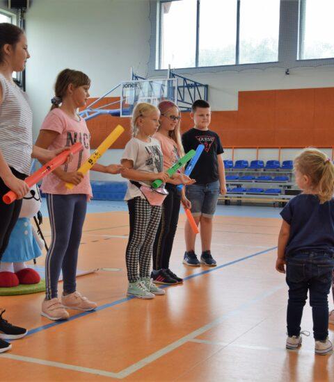 cztery dziewczynki i chłopiec stojący w rzędzie, na przeciwko stoją dwie małe dziewczynki