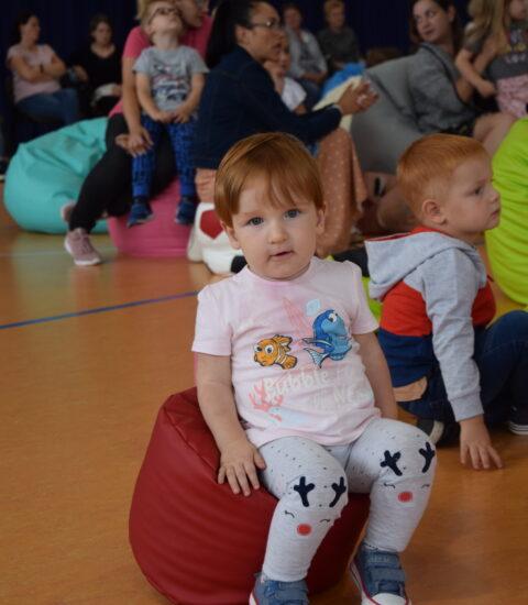 mała dziewczynka siedzi na czerwonej pufie, w tle dzieci na kolorowych pufach
