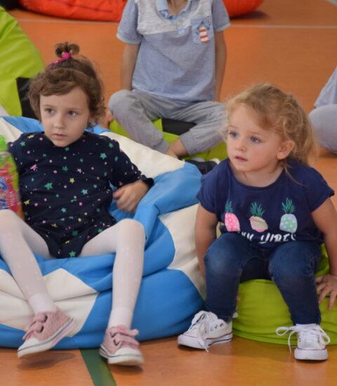 dwie dziewczynki siedzą na kolorowych pufach