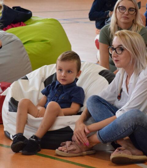 kobieta siedzi na podłodze, obok chłopiec na pufie